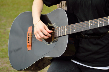 acoustical: Young woman playing a black acoustical guitar in outside setting.