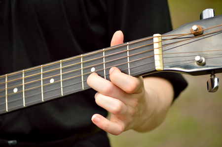 fingering: Guitarist playing finger style and fingering D note on fretboard of guitar.