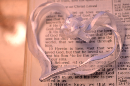 first day: White heart layed over Bible page of First John 4:10. Good Valentines Day or wedding or anniversary background. White ribbon shaped in heart and knotted in middle. Stock Photo