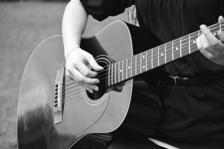 bluegrass: Young woman playing a black acoustical guitar in outside setting.
