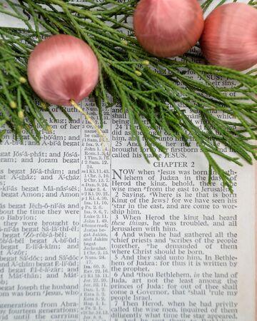 vangelo aperto: La storia di Natale, come ha detto nel Vangelo di Matteo capitolo 2, aperto Bibbia con verde cedro e antichi ornamenti di seta rosa.