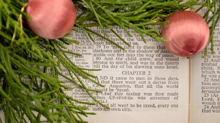 Open Bible, with greenery and ornaments. Bible open to Gospel of Luke, chapter 2, the story of the birth of Christ.