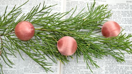 isaiah: Bible open to prophecy of birth of Christ in Isaiah 9, with cedar greenery and ornaments on top of pages.