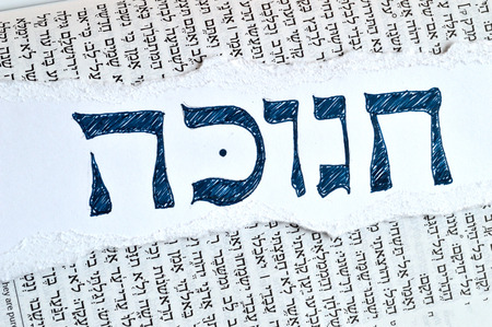 hebrew: Hebrew word hanukkah or chanukah. Jewish holiday, festival of lights. Background is the hebrew text of the book of Isaiah in the tanach.