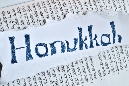 hebrew: Hebrew word hanukkah. Jewish holiday, festival of lights. Background is the hebrew text of the book of Isaiah in the tanach.