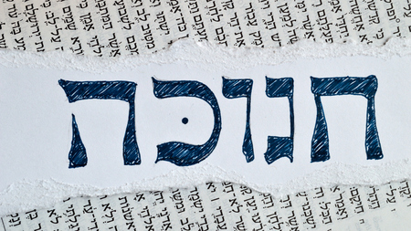 hebrew script: Hebrew word hanukkah or chanukah. Jewish holiday, festival of lights. Background is the hebrew text of the book of Isaiah in the tanach.