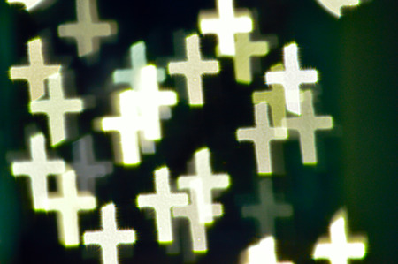 redemption: Bokeh or defocused image of lights shaped like little crosses in green and yellow colors - good St. Patricks day background. Stock Photo