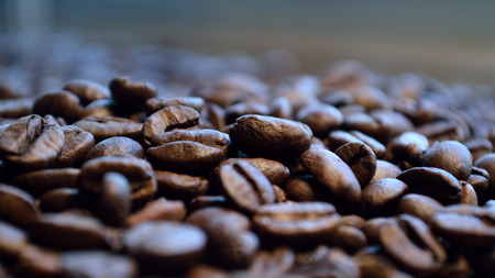 Lots of coffee beans spread out, in closeup.
