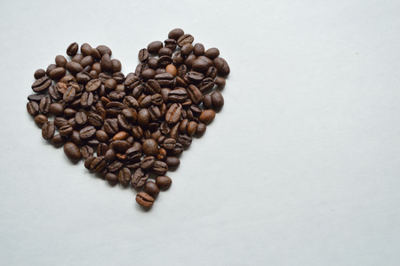 Coffee beans in the shape of a heart against a white background Stock Photo
