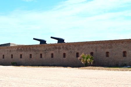 An old historical, military, brick fort on a beach in America, with two cannons pointing to the left atop the brick forts wall. Editorial