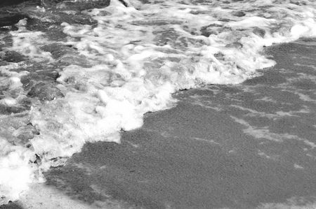 Black and white photo of the foamy waves of the ocean washing on the sandy beach Banco de Imagens