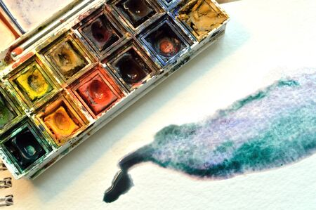 Used artist's watercolor palette, on watercolor paper with example of wet on wet technique of a fluid watercolor wash