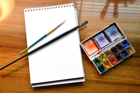 Art supplies: pad of watercolor paper, watercolor pallate with cakes of watercolor paint and two paintbrushes, ready to begin painting with. Real art supplies in a real artist's studio