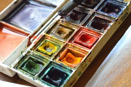 Closeup of compact, travel size, watercolor palette. Real artists stuido supplies, well used.