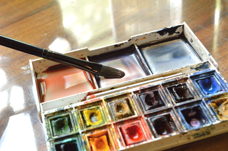 Closeup of compact, travel size, watercolor palette. Real artist's stuido supplies, well used.