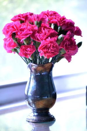 Bright pink carnations, cut flower arrangement, in heirloom silver vase. 写真素材