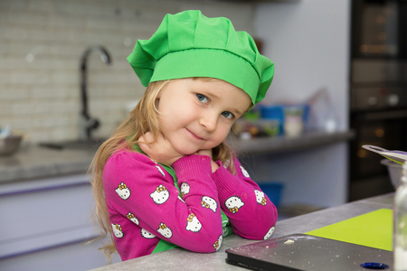 Little girl in a green cap in the kitchen