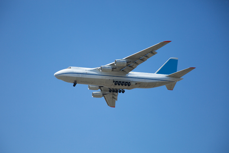 A white airplane is flying in a clear pale blue sky