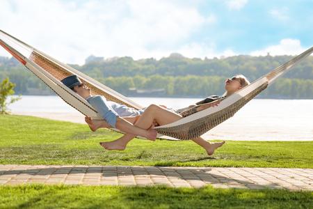 Zufriedene Paare, die in einer Hängematte auf Hintergrund des Grases und des blauen Himmels sich entspannen