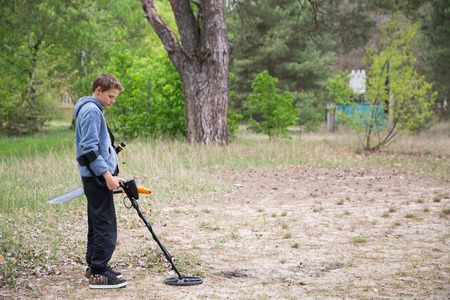 tresure: boy is looking for valuables with a metal detector Stock Photo