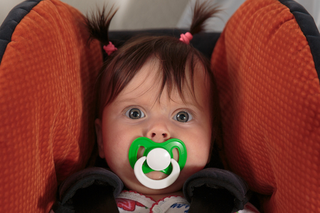 Cute adorable baby girl with babys dummy
