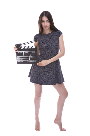 footage: Beautiful barefoot woman holding a movie clapper. Girl helps in shooting a movie. Isolated on a white background