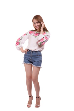 Portrait of cheerful Ukrainian girl wearing national embroidered shirt isolated on white