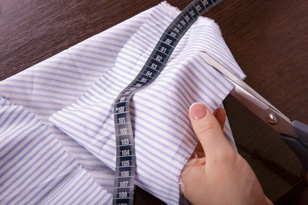 Process of sewing. Fabric cutting Centimeter Hands