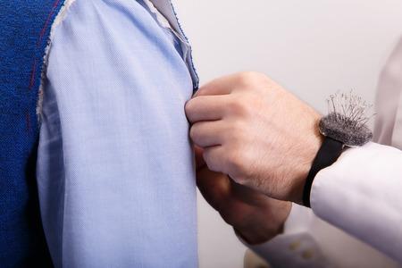 tailor designer make marks on a jacket during bespoke suit fitting