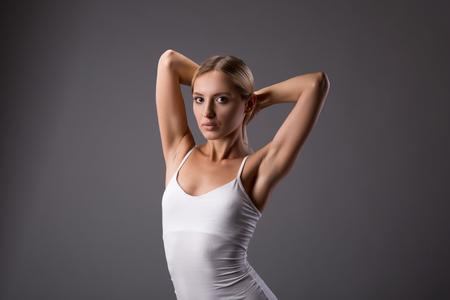 Jong tiener vrouwelijk schoonheidsportret met broodjeshanden omhoog op grijze achtergrond Stockfoto