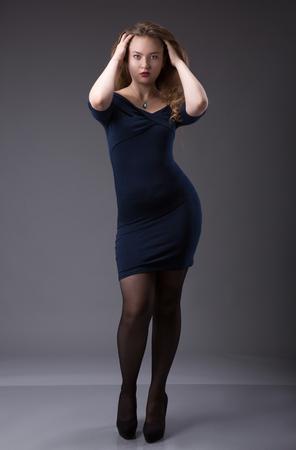 Portrait eines plus Größe weibliches Modell , das im schwarzen Kleid über grauem Hintergrund aufwirft . Schöne Frau mit curvy Figur