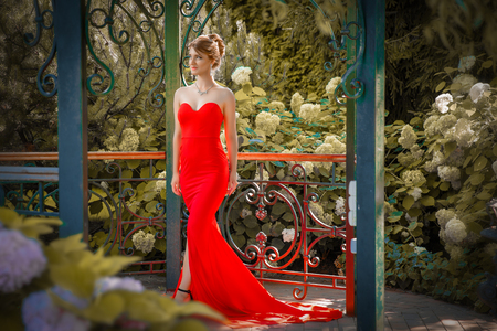 Portrait of beautiful woman in red dress outdoor in alcove