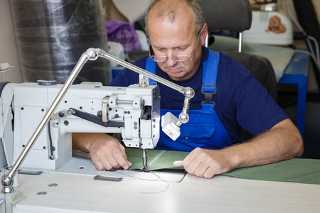 master: man seamsrtess sitting at the sewing machine in body shop