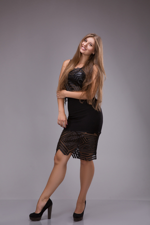 Portrait of a plus size female model posing in black dress over grey background. Beautiful woman with curvy figure.