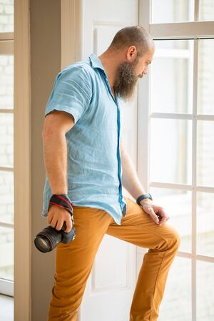 portrait of man near window. Profassional photographer hold in hand photo camera. caucasian man with beard look through window frame. Full-lenght window, Man staying