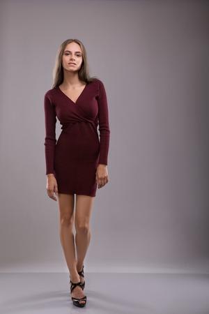Beautiful Brunette Woman dreesed burgundy Dress Stock Photo