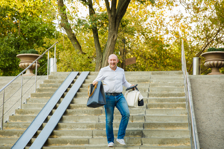 bald man with smiling happy face descending the stairs and holding shopping bag