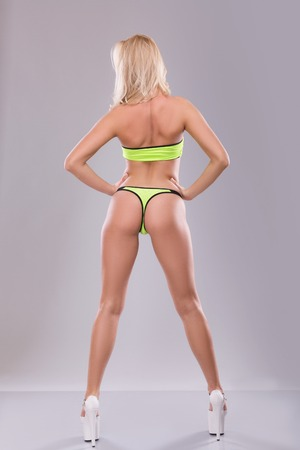 Beautiful blonde in lime green Underwear stands with his back over gray background