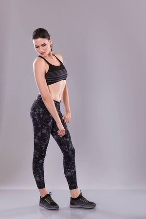 Fitness woman in black tank top and leggings, studio shot over gray bacground