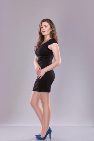 Porträt einer plus Größe weiblichen Modell posiert in schwarzem Kleid über grauem Hintergrund. Schöne Frau mit curvy Figur.