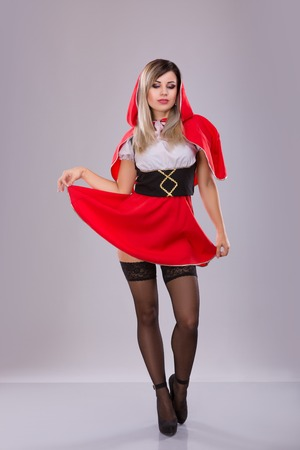 Woman with red hood over gray background. Studio shoot Stok Fotoğraf