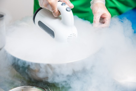 Chef is cooking ice cream with liquid nitrogen by mixer, catering event. molecular kitchen Stock Photo - 87970387