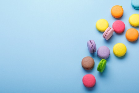 A photo of colorful macarons, shot from above on a blue background , with a place for text