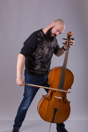 soloist: Cellist playing classical music on cello. bearded man fooling around with a musical instrument over gray background