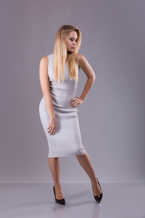 Blonde woman dressed in gray dress staying over gray background. Studio shoot