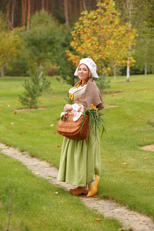 smyling peasant woman walks with a basket in park