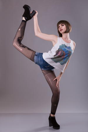 bizzare woman posing in torn pantyhose over gray background