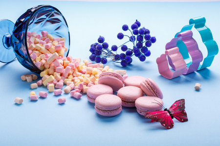 marshmallow and macaroons pouring out of jars. blue background. selective focus.