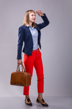 girl in red pants with a leather bag looking into the distance over gray background Stock Photo