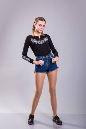Young woman with pigtails wearing black embroidery and shorts over gray background. studio shoot